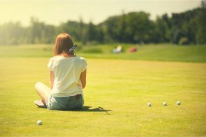 A woman sitting on the golf course